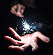 Picture of an outreached hand with a sparkler in it with the other hand behind it.