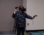A child with a VR helmet and hand controllers.