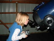Young girl looking through the large Fox Telescope while holding an astronomy book.