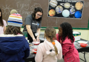 A woman helping 3 children at the MSU Observatory booth with the planets in the background.