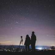 two people with a telescope at night