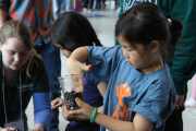 A girl planting a seed in a cup at the science festival booth.
