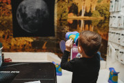 Child looking through binoculars at an image of the moon.